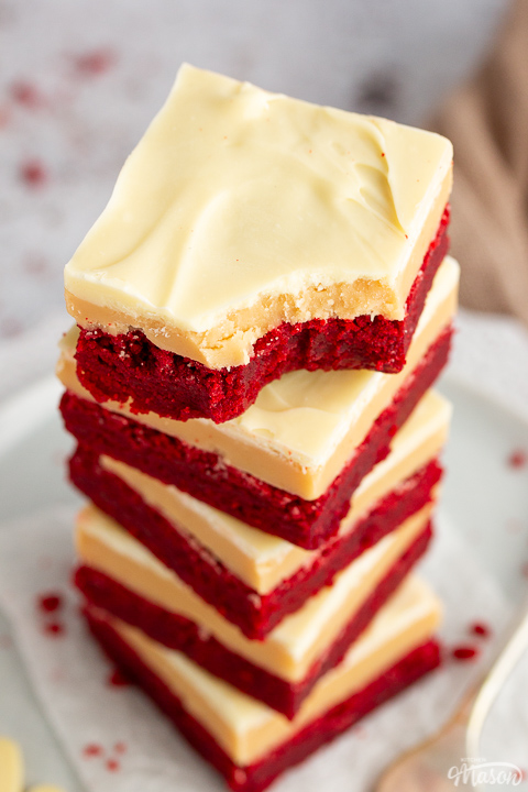 A stack of 5 red velvet millionaire brownies set on two stacked plates with a fork on the side. The top one has a bite taken out of it.
