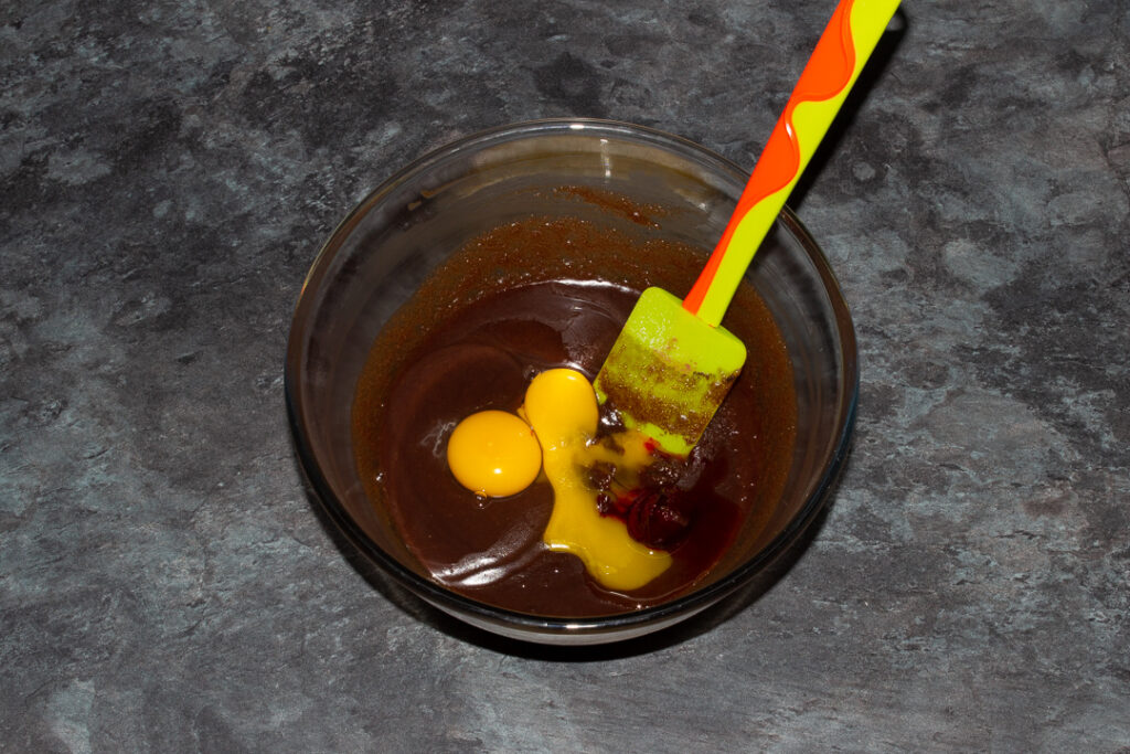 Egg, egg yolk, vanilla and red food colouring gel on top of a melted butter, sugar and cocoa powder mixture in a glass bowl with a green spatula.