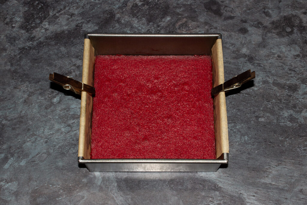 Baked red velvet brownie in a lined square baking tin with a peg on each side.