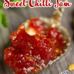A close up of sweet chilli jam on a gold spoon set on a grey wooden backdrop with lettuce and chilli flakes in the background.