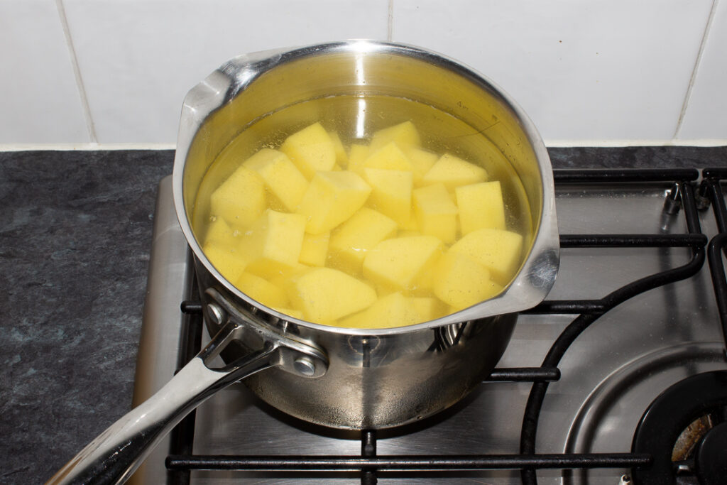 Chopped potatoes in a pan of cold salted water on the hob