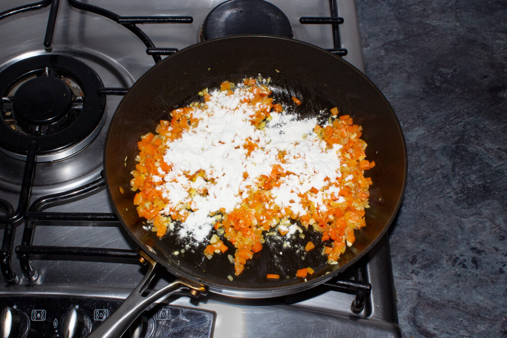Onion, carrot, garlic and flour cooking in oil in a frying pan on the hob