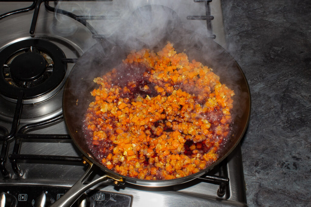 Onion, carrot, garlic, flour and red wine cooking in a frying pan on the hob