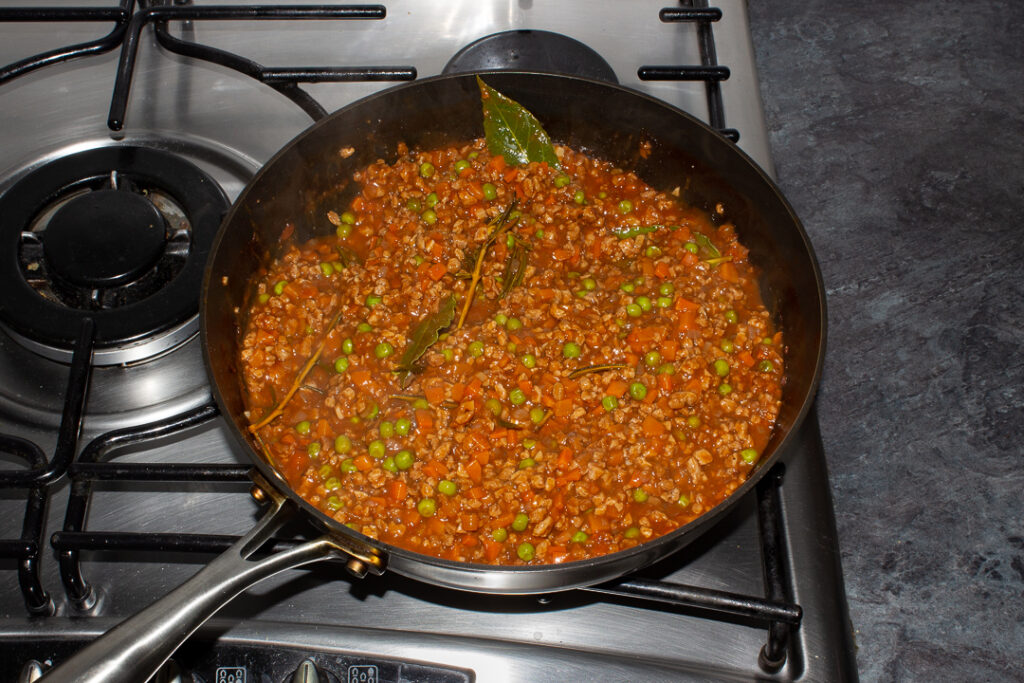 Thickened vegetarian shepherd's pie mince ingredients together in a frying pan on the hob after being cooked