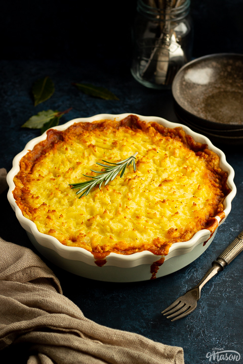 Vegetarian shepherd's pie in a dish topped with a sprig of rosemary. There's cutlery, dark bowls and a light brown napkin set over a deep blue backdrop.