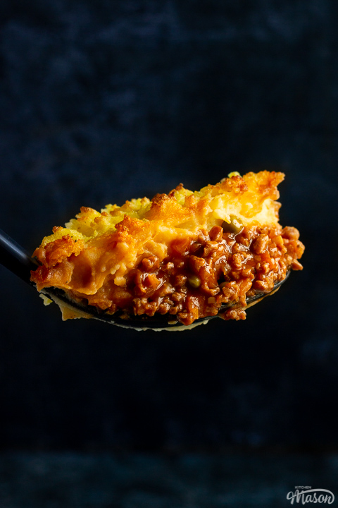 A close up of a large spoonful of vegetarian shepherd's pie up against a deep blue backdrop