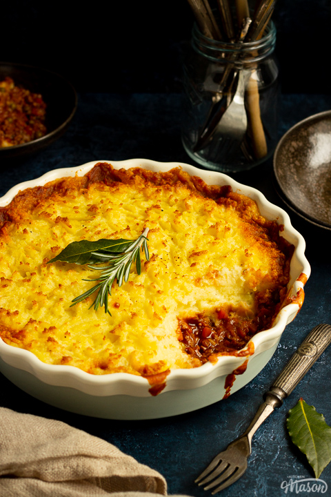 Vegetarian shepherd's pie in a dish with a spoonful taken out of it and a sprig of rosemary on top. There's cutlery, dark bowls and a light brown napkin set over a deep blue backdrop.