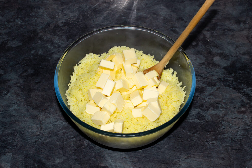 Boiled potato that's been pressed through a potato ricer and cubed butter in a glass bowl on a kitchen worktop