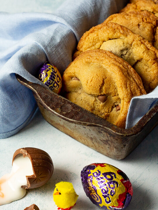 Creme Egg cookies in a bread tin lined with a pale blue napkin surrounded by whole and broken Creme Eggs. Set on a pale blue backdrop with a tray of whole Creme Eggs and a yellow Easter chick in the background.