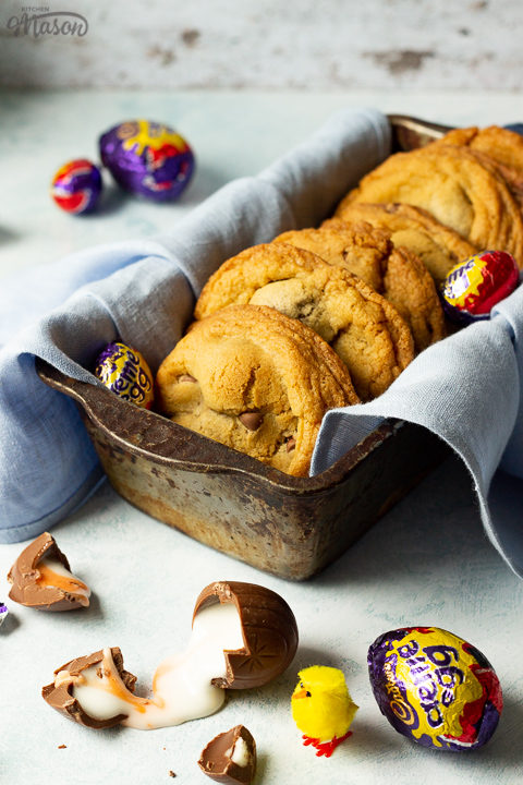 Creme Egg cookies in a bread tin lined with a pale blue napkin surrounded by whole and broken Creme Eggs. Set on a pale blue backdrop with a yellow Easter chick in the background.