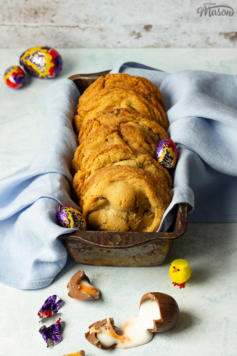 Front view of Creme Egg cookies in a bread tin lined with a pale blue napkin surrounded by whole and broken Creme Eggs. Set on a pale blue backdrop with a yellow Easter chick in the background.