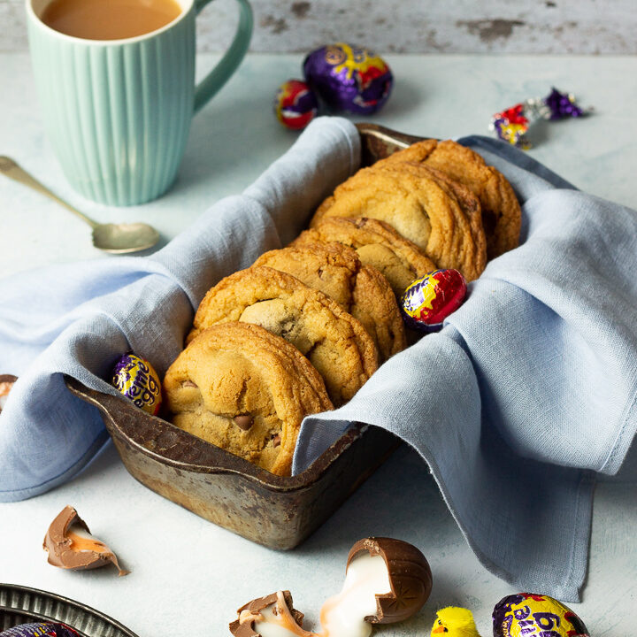 Creme Egg cookies in a bread tin lined with a pale blue napkin surrounded by whole and broken Creme Eggs. Set on a pale blue backdrop with a tray of whole Creme Eggs, a mug of tea and a yellow Easter chick in the background.
