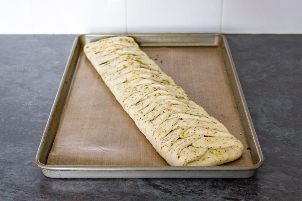 An unbaked stromboli on a lined baking tray. Brushed with olive oil and dried herbs