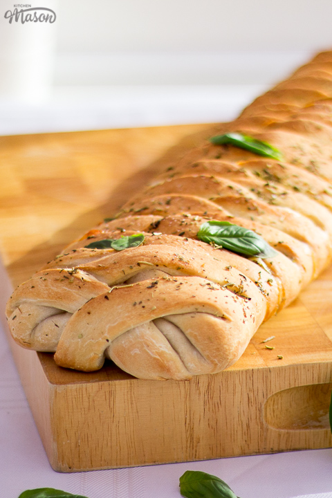 Baked stromboli on a wooden chopping board scattered with fresh basil leaves