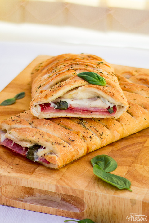Baked stromboli cut in half on a wooden chopping board scattered with fresh basil leaves