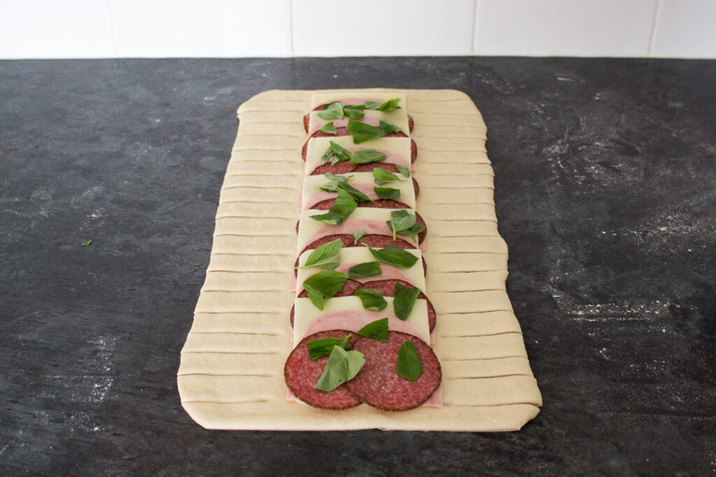 Pizza dough rolled out to a rectangle, topped with layered mozzarella, salami, ham and basil leaves on a lightly floured work surface. The dough has slices either side of the filling.