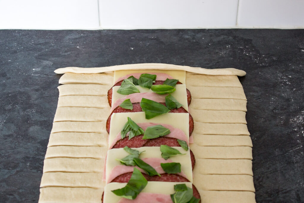 Pizza dough and fillings being folded into a latticed stromboli