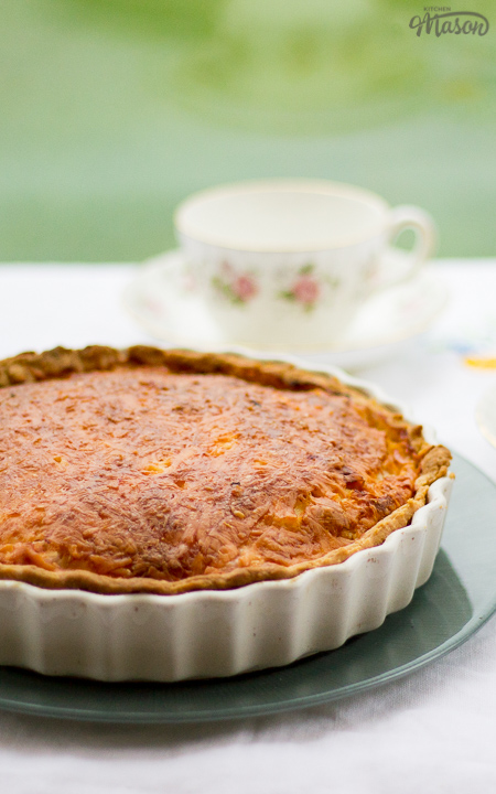 Gran's ham and cheese quiche in a white baking dish on a green plate. Set on a white floral table cloth with teacups and a saucer in the background.