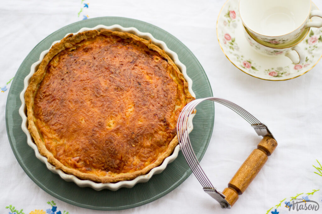 Gran's ham and cheese quiche in a white baking dish on a green plate. Set on a white floral table cloth with a pastry blender, teacups and a saucer in the background.