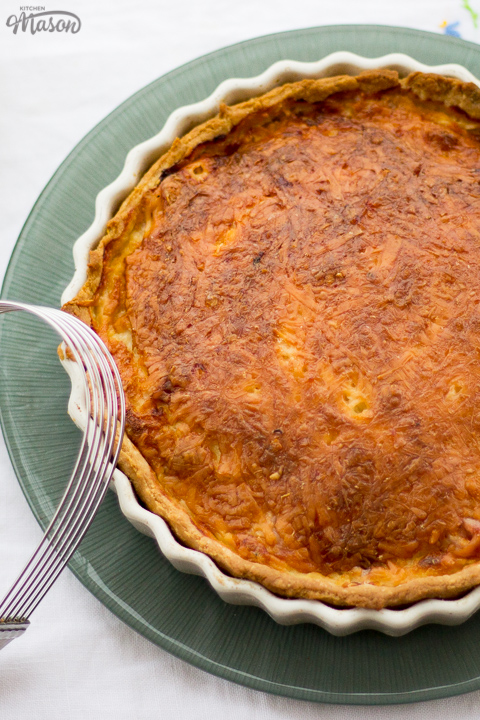 Gran's ham and cheese quiche in a white baking dish on a green plate. Set on a white floral table cloth with a pastry blender in the background.