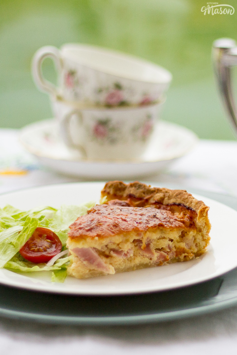 A slice of Gran's ham and cheese quiche and a side salad on a white plate set over a larger green plate. Set on a white floral table cloth with a teapot, cups and saucers in the background.
