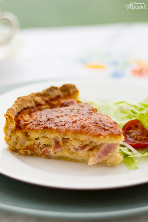 A slice of Gran's ham and cheese quiche and a side salad on a white plate set over a larger green plate. Set on a white floral table cloth with cups and saucers in the background.