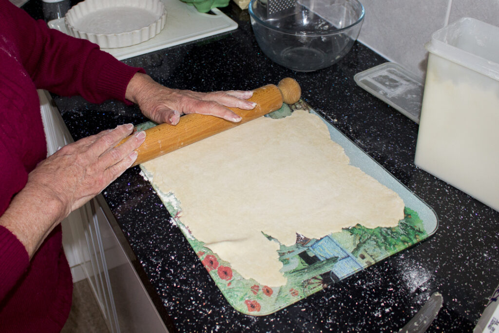 Gran rolling out the pastry with a rolling pin on a kitchen worktop