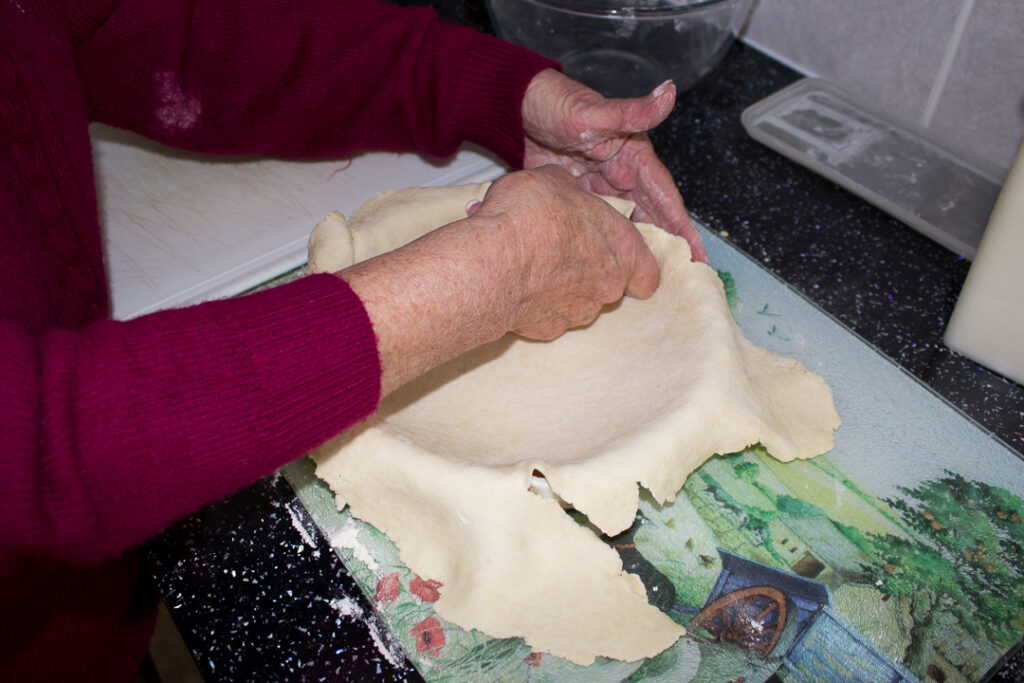 Gran pressing the pastry into the baking dish on a kitchen worktop
