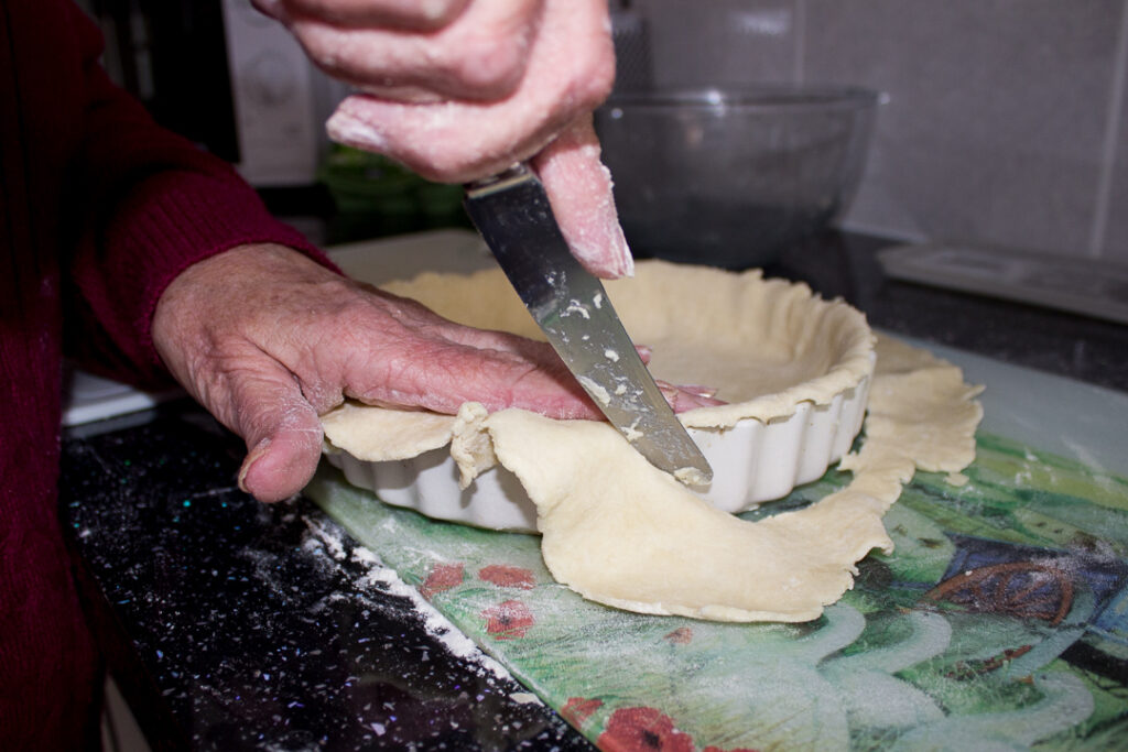 Gran trimming off the excess pastry with a knife