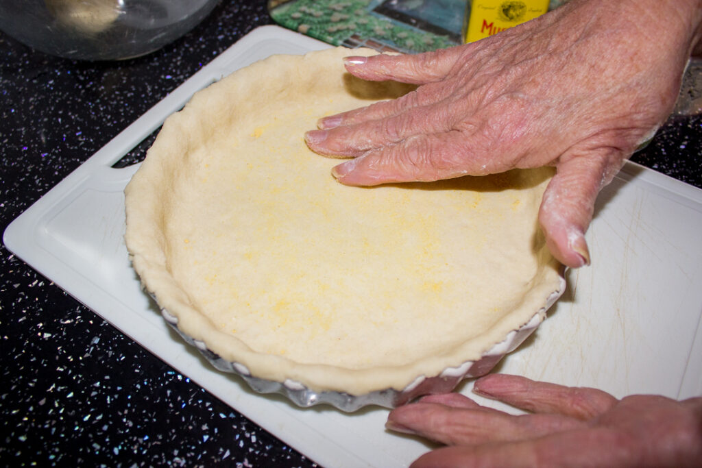 Gran spreading mustard powder over the base of the pastry case