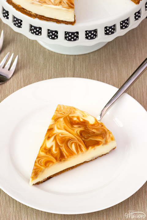 A slice of no bake Biscoff cheesecake on a white plate with a cake slice underneath. The rest of the cheesecake is on a cake stand in the background along with 2 forks.