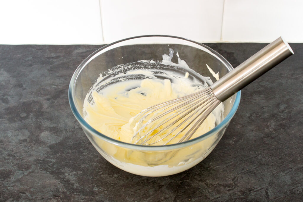 Cream whipped to stiff peaks in a glass bowl with a hand whisk