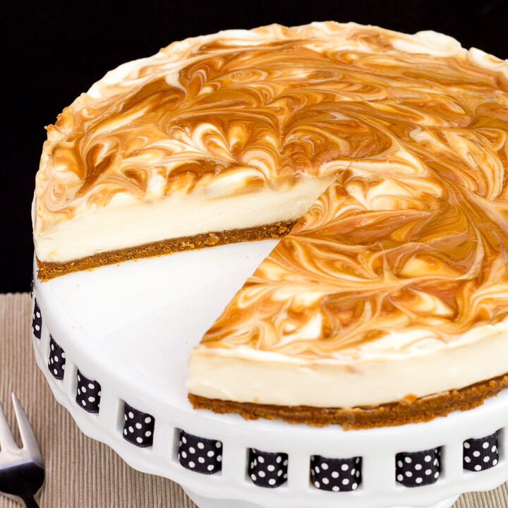 Close up of a Biscoff cheesecake with a slice out of it, set on a cake stand against a black backdrop.