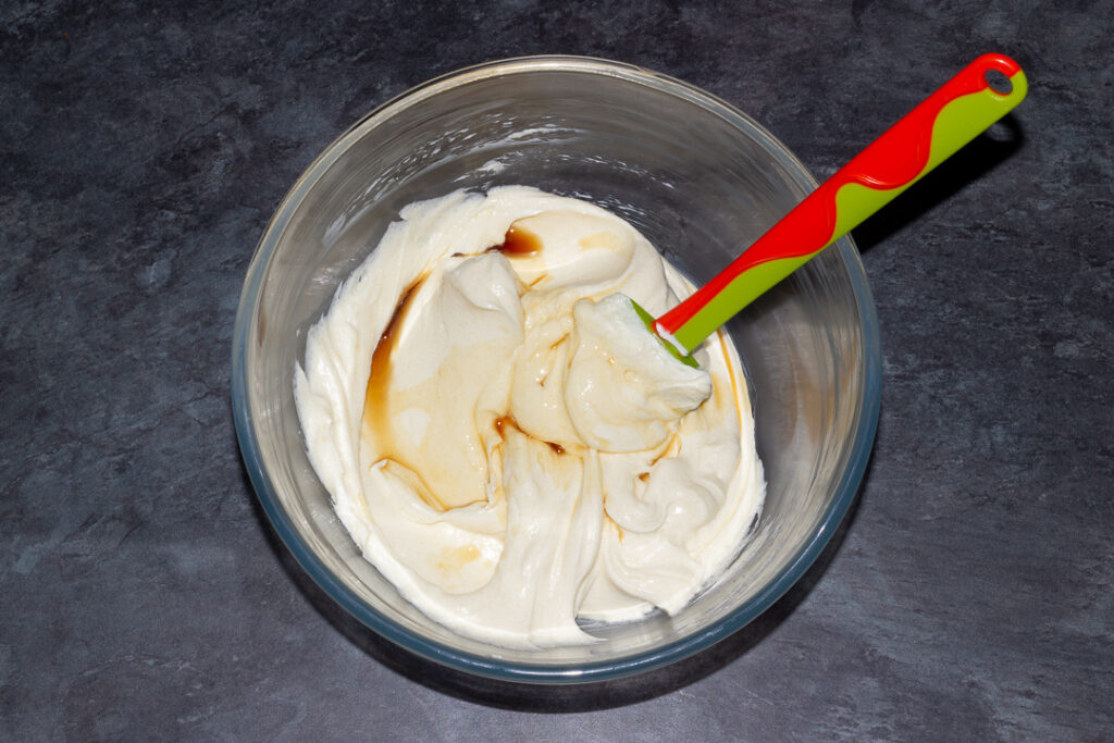 Cream cheese and caster sugar beaten together with vanilla in a glass bowl with a spatula on a kitchen worktop