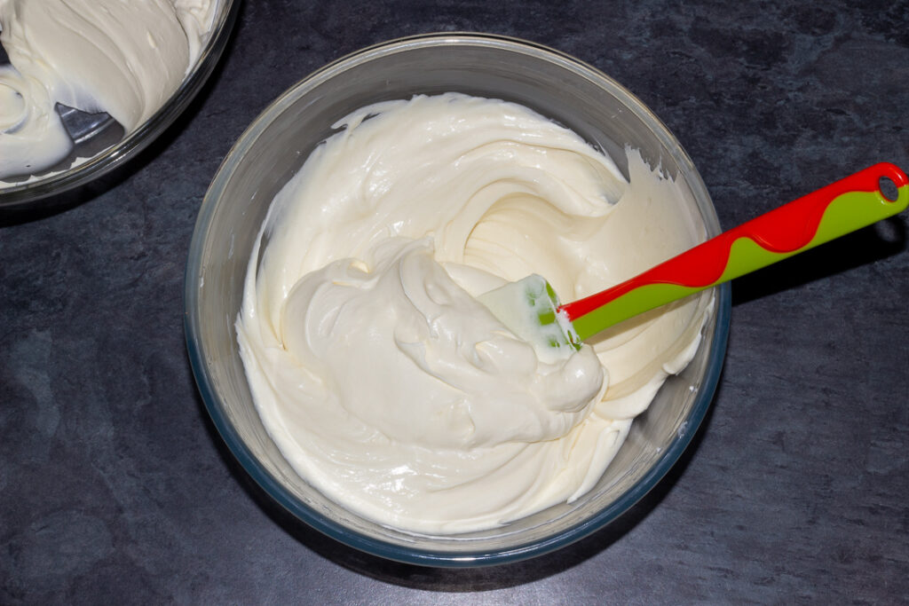 Whipped cream being folded into the cream cheese mixture in a glass bowl with a spatula on a kitchen worktop.
