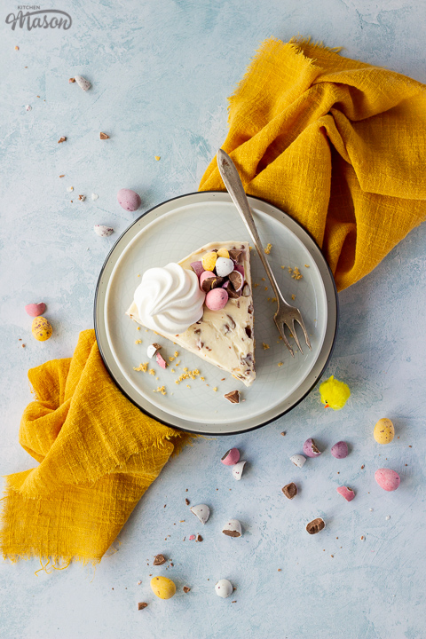 A slice of no bake Mini Egg cheesecake topped with a mini meringue nest and chopped Mini Eggs on two stacked plates with a fork on the side. There are chopped mini eggs and a yellow linen napkin set over a light blue background.