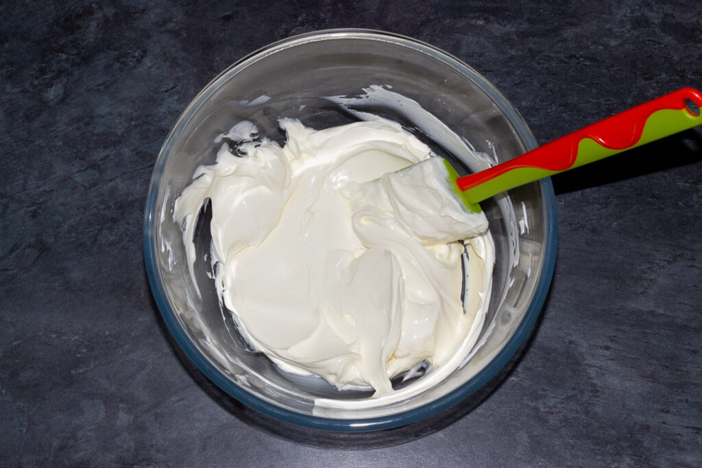 Cream cheese beaten until softened with a spatula in a glass bowl on a kitchen worktop.