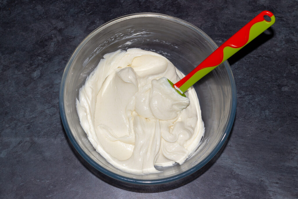 Cream cheese and caster sugar beaten together in a glass bowl with a spatula on a kitchen worktop