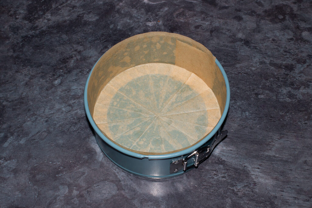 A springform pan lined with baking paper on the base and sides on a kitchen worktop.