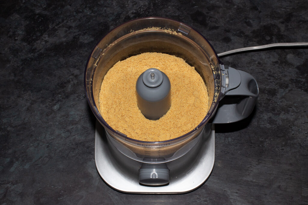 Crushed malted milk biscuits in a food processor on a kitchen worktop