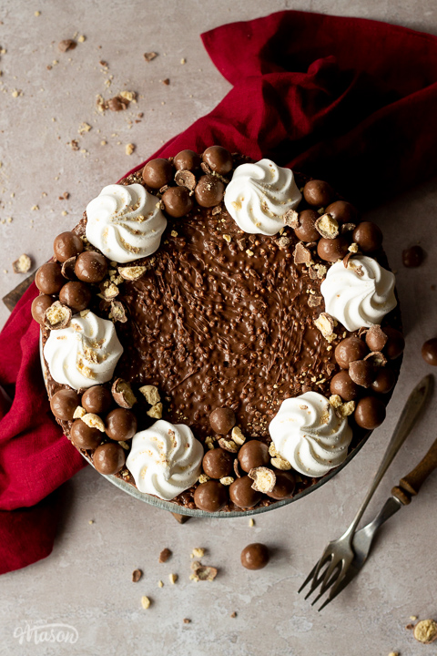 Birds eye view of a no bake Malteser cheesecake on a cake stand with crushed Maltesers scattered around, 2 forks and a red linen napkin in the background. Set on a light neutral backdrop.