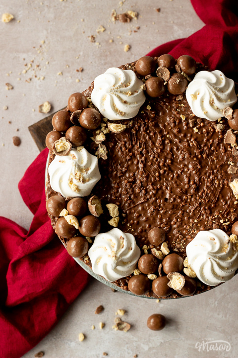 Close up birds eye view of a no bake Malteser cheesecake on a cake stand with crushed Maltesers scattered around, 2 forks and a red linen napkin in the background. Set on a light neutral backdrop.
