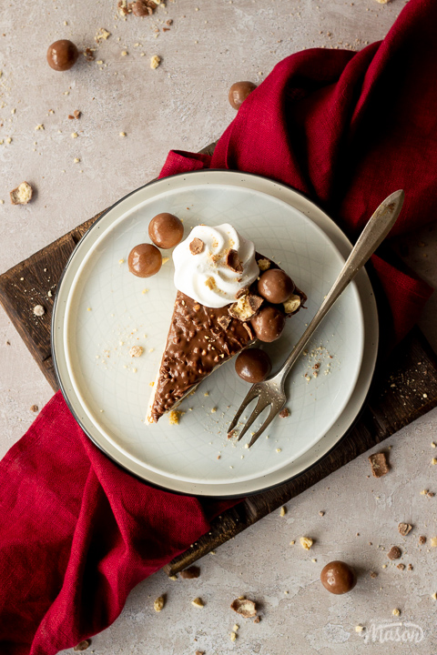 Birds eye view of a slice of no bake Malteser cheesecake on 2 stacked plates with a fork. There are crushed Maltesers scattered around and a red linen napkin in the background. Set on a light neutral backdrop.