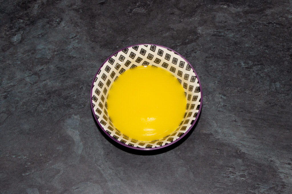 Melted butter in a small bowl on a kitchen worktop.