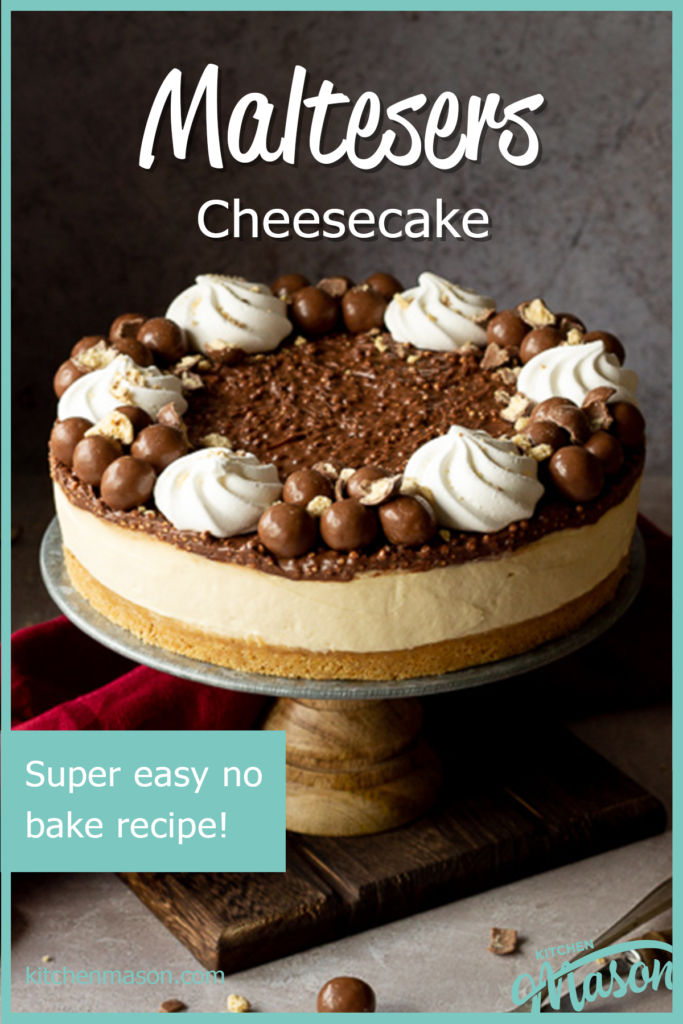 Front view of a no bake Malteser cheesecake on a cake stand. With crushed Maltesers scattered around, a red linen napkin and 2 forks. Set on a light neutral backdrop.