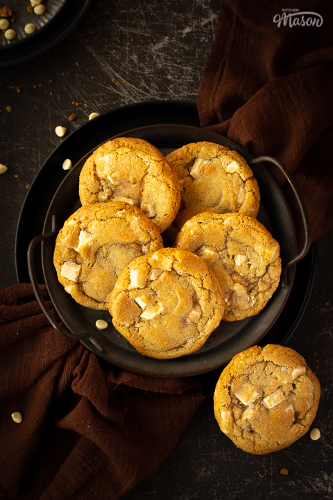 5 white chocolate chip cookies on an iron handled plate and 1 cookie to the side, with a brown linen napkin underneath. Set on a scratched black metal backdrop with white chocolate chips scattered around.