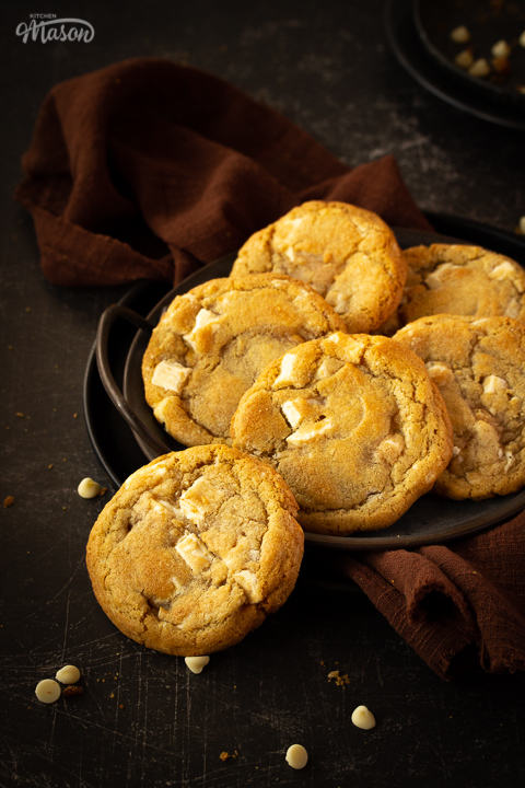 Front view of 5 white chocolate chip cookies on an iron handled plate and 1 cookie to the side, with a brown linen napkin underneath. Set on a scratched black metal backdrop with white chocolate chips scattered around.