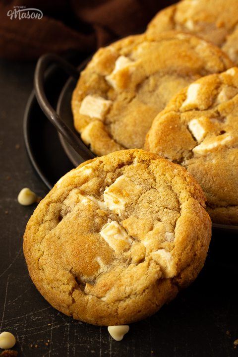 Close up of 1 white chocolate chip cookie with an iron handled plate in the background that has 3 more cookies on it. Set over a brown linen napkin and a scratched black metal backdrop.