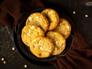 6 white chocolate chip cookies on an iron handled plate with a brown linen napkin underneath. Set on a scratched black metal backdrop.