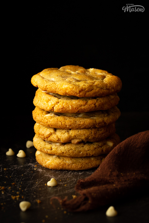A stack of 6 white chocolate chip cookies set on a scratched black metal background with a brown linen napkin and white chocolate chips scattered around.